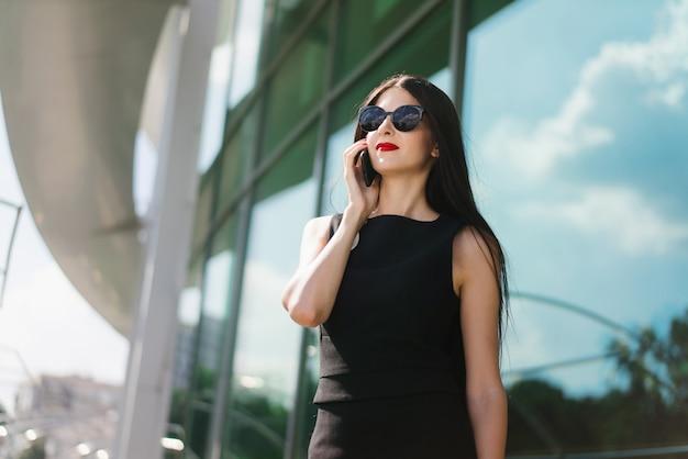 Деловая женщина с красными губами в элегантном черном платье и солнцезащитных очках стоит перед высокотехнологичным стеклянным зданием бизнес-центра и разговаривает по мобильному телефону