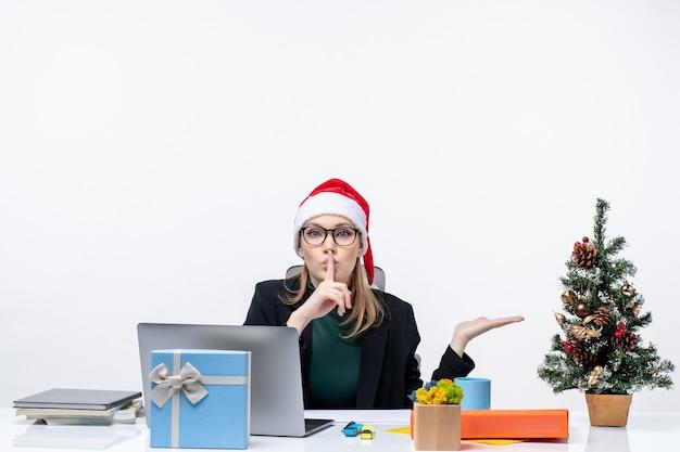 Donna d'affari con un cappello di babbo natale seduto a un tavolo con un albero di natale e un regalo su di esso e indicando qualcosa sul lato sinistro qualcosa e facendo un gesto di silenzio in ufficio