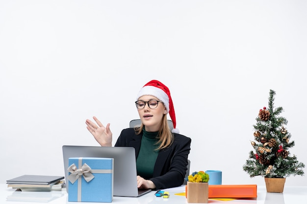 Business woman with a santa claus hat sitting at a table with a christmas tree and a gift
