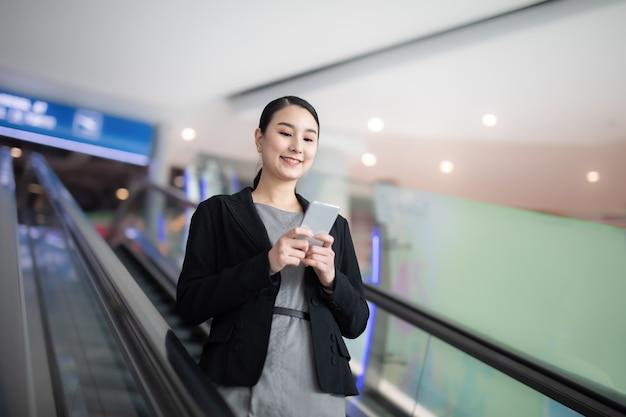 정장을 입은 비즈니스 우먼은 단말기에서 스마트 폰을 사용합니다.