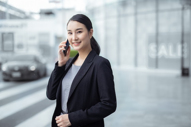 정장을 입은 비즈니스 우먼은 거리에서 스마트 폰을 사용합니다.