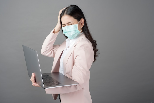 Business woman with surgical mask is holding laptop computer