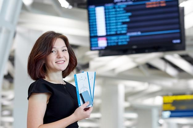 Деловая женщина с билетами и кредитной картой ждет вылета возле информационного табло в аэропорту