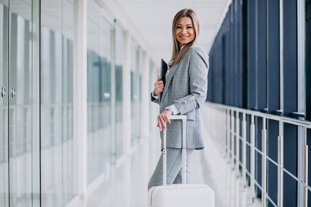 Business woman with travel luggage in airport, holding laptop