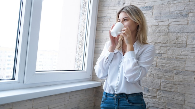 Business woman with white cup of coffee looking out the window - brick wall