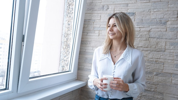 Деловая женщина с белой чашкой кофе, глядя в окно - кирпичная стена