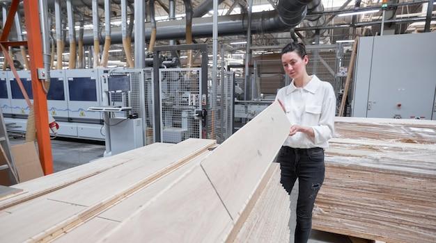 Деловая женщина, работающая на плотницком заводе с помощью планшетного пк