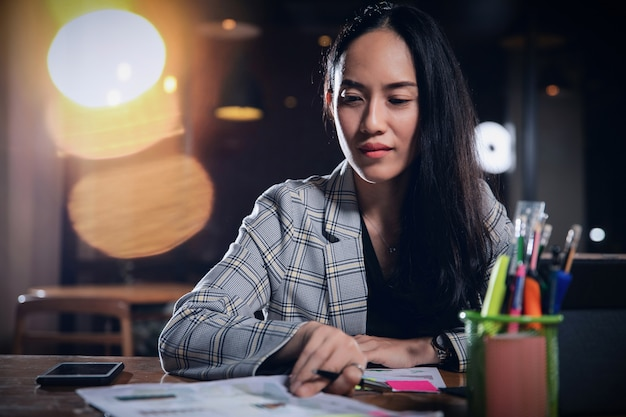 Business woman working alone in office at night