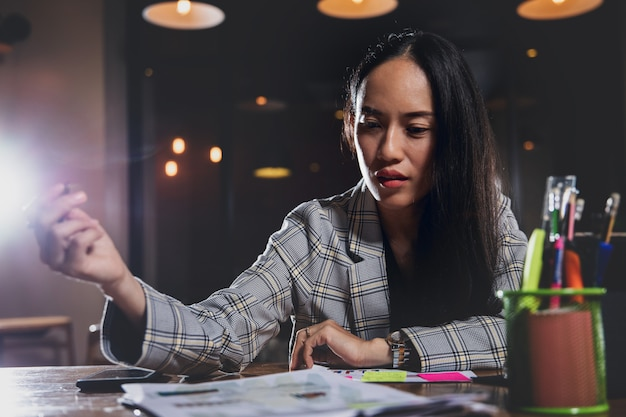 Business woman working alone in office at night.