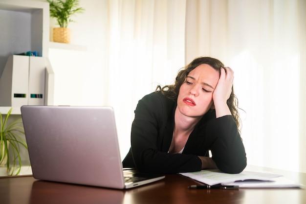 Деловая женщина, работающая на своем компьютере и подчеркнутая в офисе усталая женщина-предприниматель