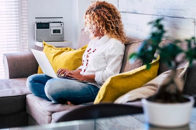 집에서 일하는 비즈니스 여자는 현대 노트북 컴퓨터 인터넷이 연결된 소파에 앉아-프리랜서와 디지털 유목민 트렌디 한 대안 사람들을위한 행복한 무료 라이프 스타일