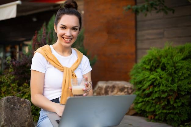 거리에 컴퓨터에서 일하는 비즈니스 여자.