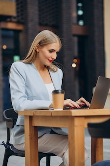 Business woman working on computer in a cafe and drinking coffee