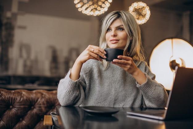 Donna d'affari che lavora al computer in un bar
