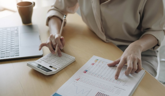 Business woman working in finance and accounting analyze financial budget with calculator and laptop computer in the office