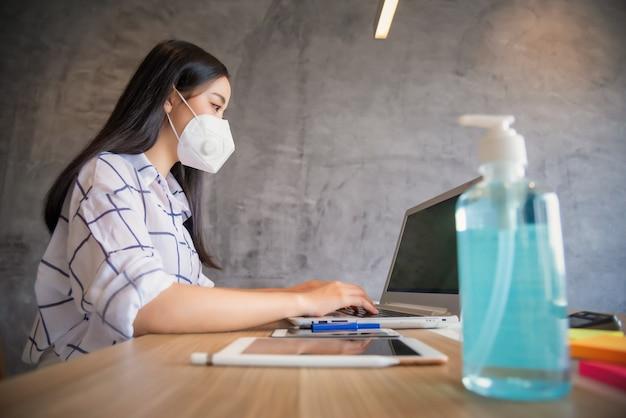 Бизнес-леди работая от дома нося защитную маску и используя портативный компьютер. коронавирус вспышка
