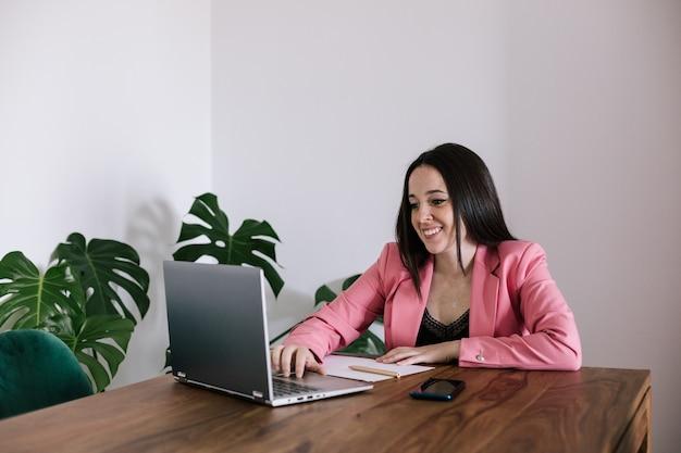 작동하는 비즈니스 우먼. 그는 컴퓨터에 입력하고 있습니다. 그녀는 우아한 핑크색 정장을 입고있다