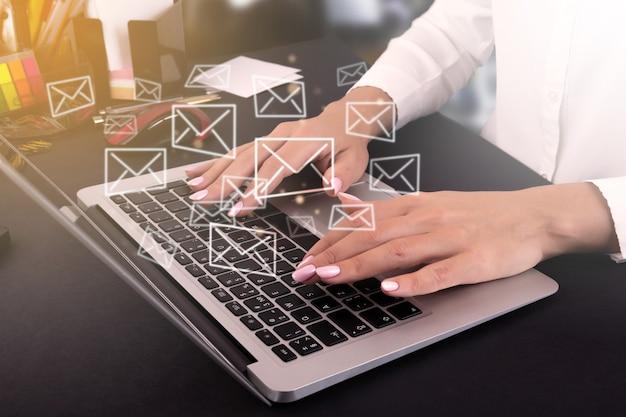 가상 화면에 이메일 아이콘이 있는 노트북을 사용하여 사무실에서 일하는 비즈니스 여성, 이메일, 직접 마케팅, 온라인 메시지, 이메일 개념을 보냅니다. 고품질 사진