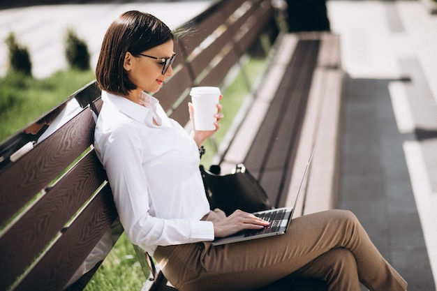 Donna di affari che lavora al computer portatile fuori dal parco