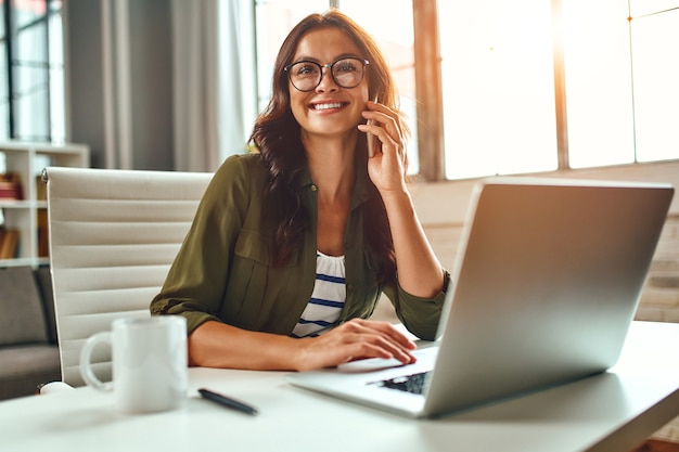 Business woman working at a laptop while sitting at a table at home and talking on the phone. freelance, work from home.