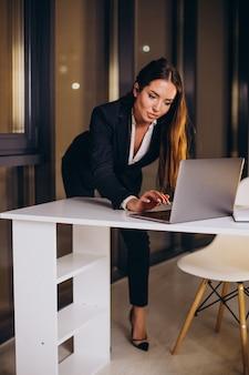 Donna d'affari che lavora fino a tarda notte in ufficio