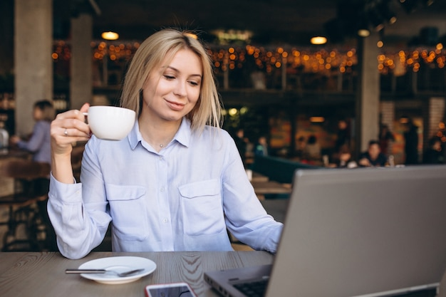 Деловая женщина, работающая на ноутбуке и телефоном в кафе