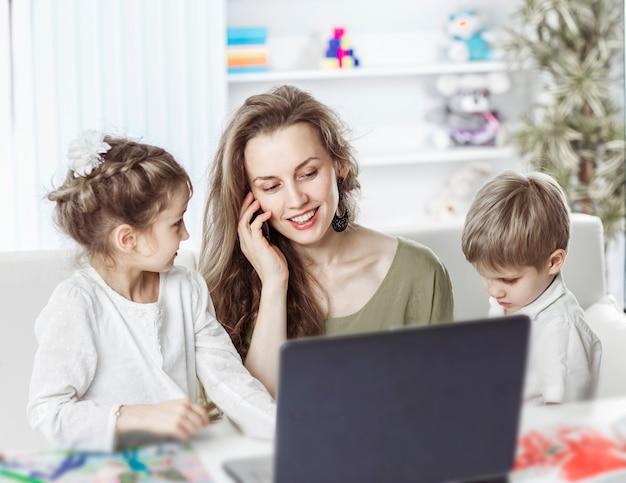 Деловая женщина работает на ноутбуке и разговаривает на смартфоне рядом со своими детьми