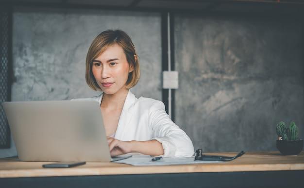 Деловая женщина, работающая на ноутбуке, поиск в интернете, просмотр информации, сидя и работая за столом