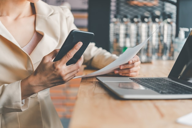 Деловая женщина, работающая на смартфоне и ноутбуке, ищет в интернете, просматривает информацию, сидя и работая за столом