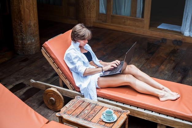 Деловая женщина, работающая на компьютере на открытом воздухе в отпуске