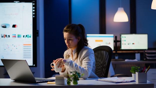초과 근무 확인 팀 프로젝트, 메모 작성, 커피 마시기, 늦은 밤 신생 회사 책상에 앉아 현대 기술 네트워크를 사용하여 재무 문서 분석을 하는 비즈니스 여성