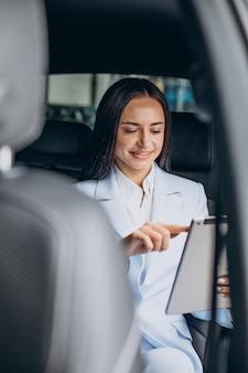 Donna d'affari che lavora su tablet nel sedile posteriore della sua auto