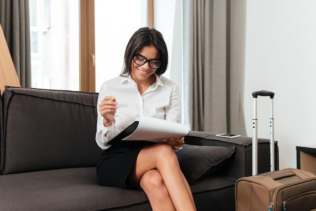 ソファーに座ってドキュメントを扱うビジネス女性