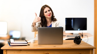 Business woman working with her laptop and with thumb up in the office