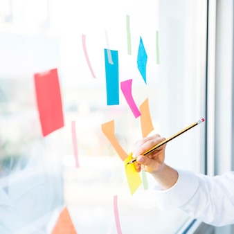 ビジネスの女性がオフィスでメモを扱う