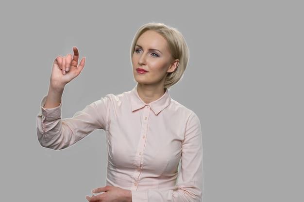 仮想画面で働くビジネスウーマン。灰色の背景に対して目に見えない仮想画面に触れているきれいなオフィスの女性。ビジネス、未来、人と技術の概念。