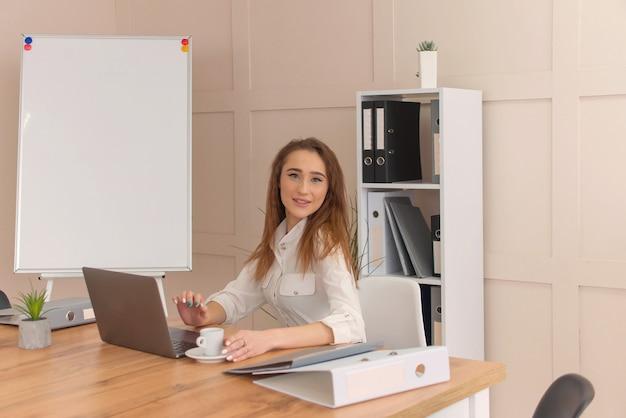 ビジネスウーマンはラップトップで働いています。オフィスで女性の肖像画。
