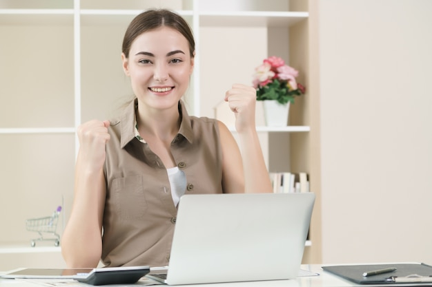 Business woman works on laptop computer expressing successful feeling.
