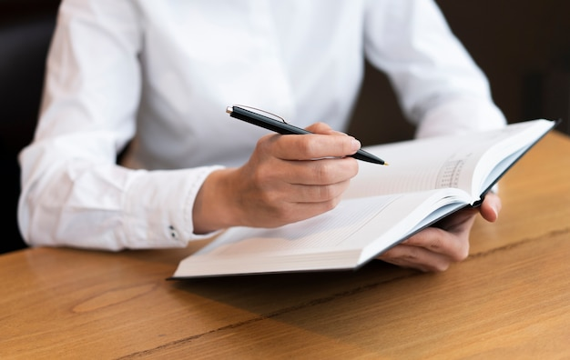 Business woman writing in agenda