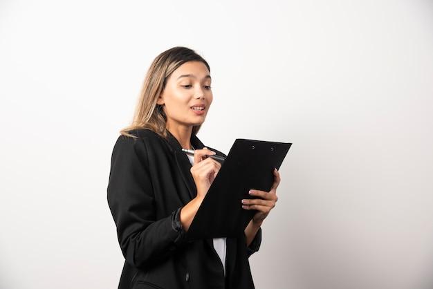 Scrittura della donna di affari negli appunti sul muro bianco.