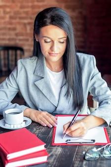 カフェで書くビジネス女性