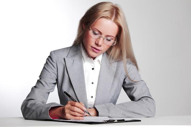 灰色の表面にノートに書くビジネスウーマン