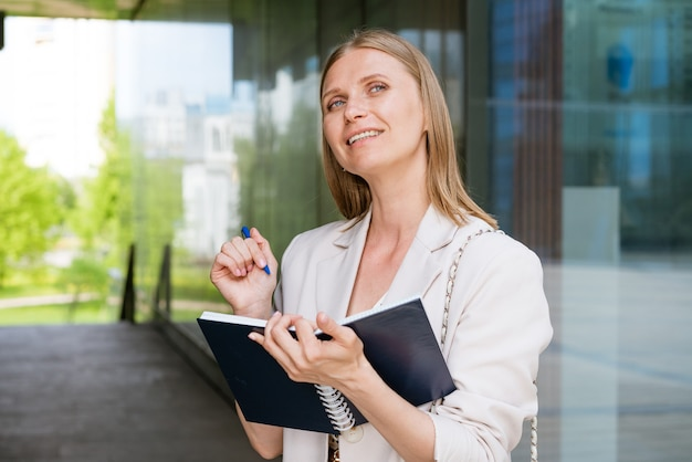 노트북에 펜으로 작성 하는 비즈니스 우먼 가벼운 재킷에 백인 성공적인 소녀 근처에 약자