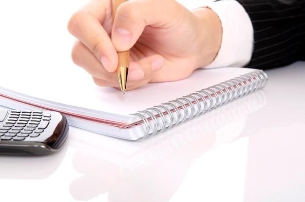 ビジネスの女性がノートにペンで書く