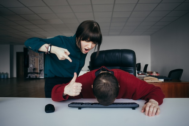 Business woman yells at his subordinate, who lowered his head and shows paletst up. the situation in the office.
