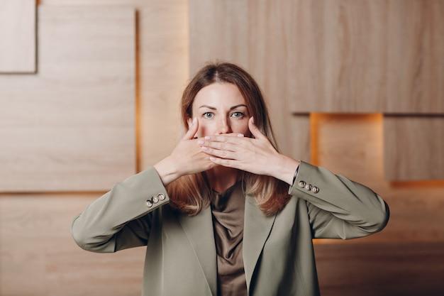 사무실에서 비즈니스 여자 젊은 성인 코치 손 팔 손바닥으로 입을 닫습니다.