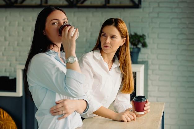 비즈니스 여성들은 회의가 시작되기를 기다리며 비즈니스 결정을 내리는 현대적인 대형 벽돌 사무실 인 커피를 마시고 있습니다. 작업 휴식.
