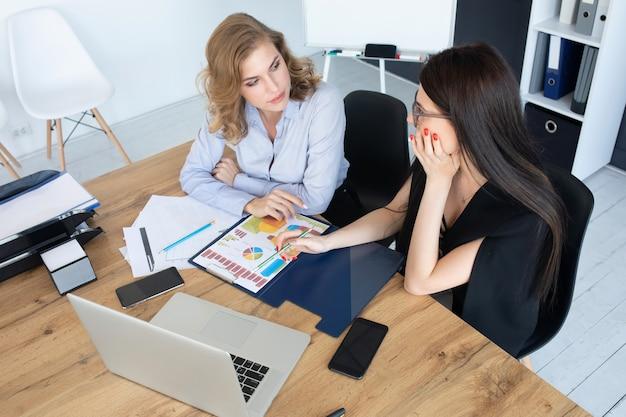 ノートパソコン、チームワークの概念に一緒に取り組んでいるオフィスの机でビジネス女性