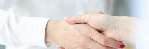 Business women colleagues shaking hands in office closeup partnership deals concept