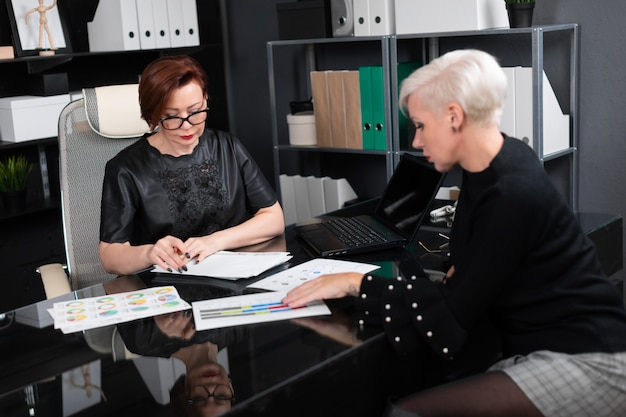 Business women discuss diagrams at desk in office